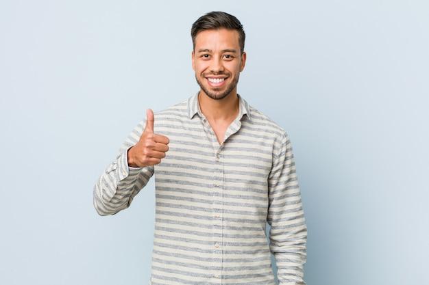 Jonge knappe filipijnse man die en duim glimlacht opheft