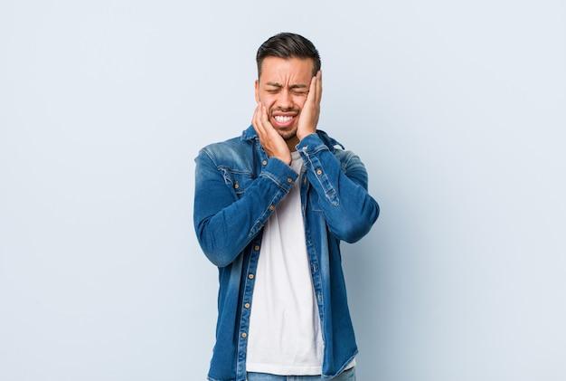 Jonge knappe filipijnse man jengelen en huilen disconsolately.