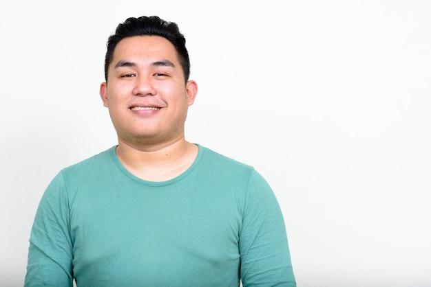 Jonge knappe filipijnse man met overgewicht tegen een witte muur
