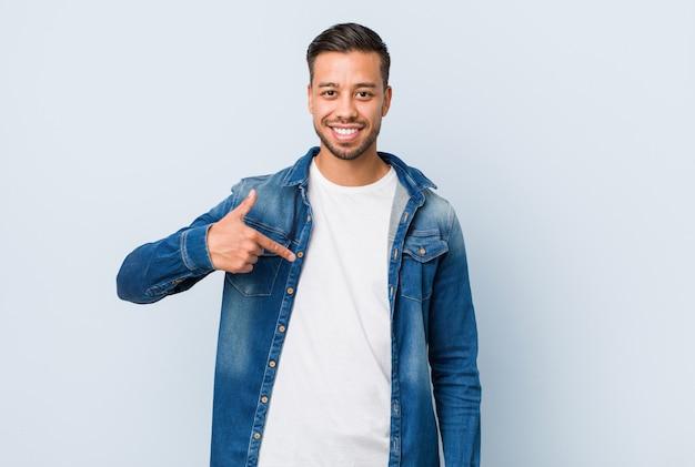 Jonge knappe filipijnse man persoon wijst met de hand naar een shirt kopie ruimte, trots en zelfverzekerd