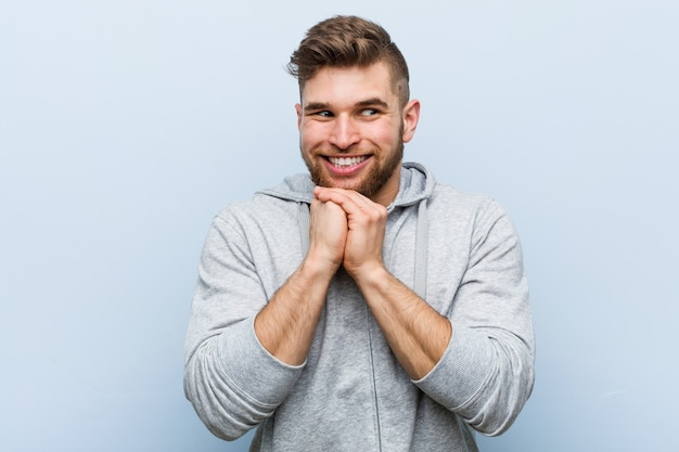 Jonge knappe fitness man houdt handen onder de kin, kijkt gelukkig opzij.