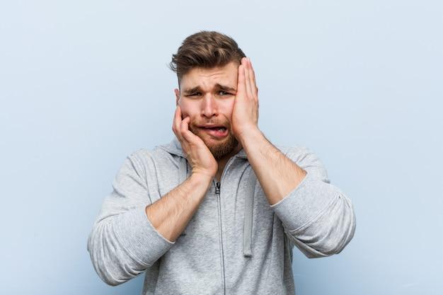Jonge knappe fitness man jengelen en huilen disconsolately.
