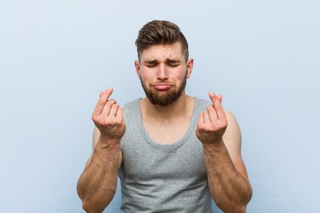 Jonge knappe fitness man laat zien dat hij geen geld heeft.