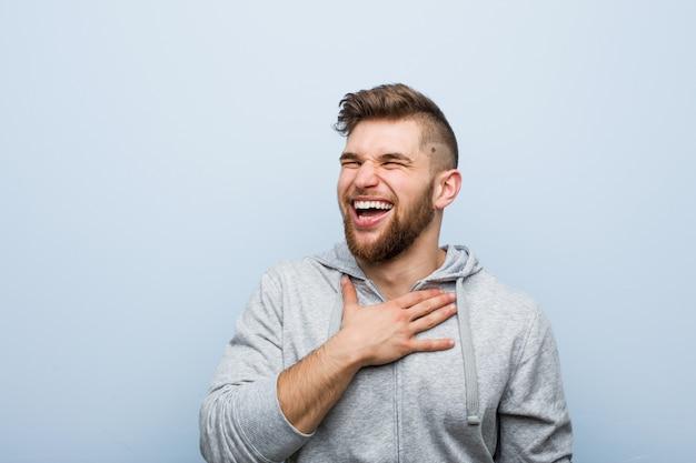 Jonge knappe fitness man lacht hardop hand op de borst te houden.
