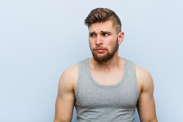 Jonge knappe fitness man verward, voelt zich twijfelachtig en onzeker.