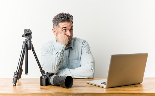Jonge knappe fotografie leraar die zich verdrietig en nadenkend voelt, kijkend naar kopie ruimte.
