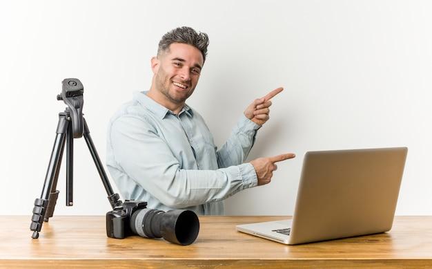 Jonge knappe fotografie leraar opgewonden wijzend met wijsvingers weg.