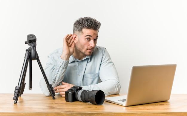 Jonge knappe fotografie leraar probeert te luisteren naar een roddel.