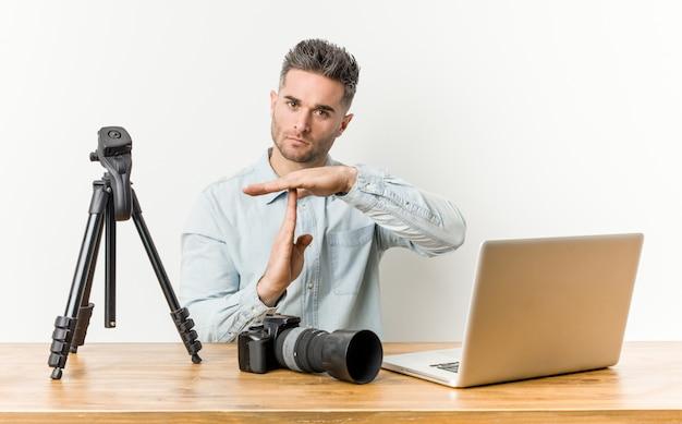 Jonge knappe fotografie leraar toont een time-out gebaar.