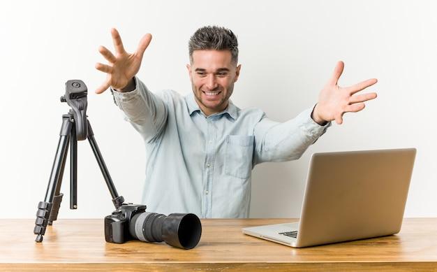 Jonge knappe fotografie leraar voelt zich zelfverzekerd en geeft een knuffel aan de camera.