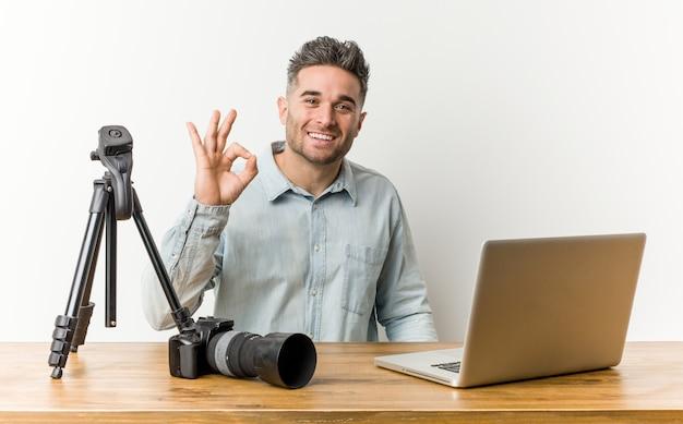 Jonge knappe fotografie leraar vrolijk en vol vertrouwen tonen ok gebaar.