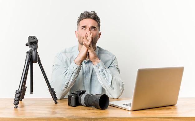 Jonge knappe fotografieleraar die een plan bedenkt, een idee opzet.