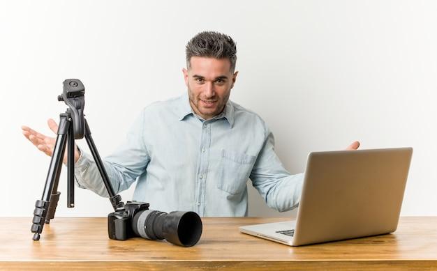 Jonge knappe fotografieleraar die een welkome uitdrukking toont.
