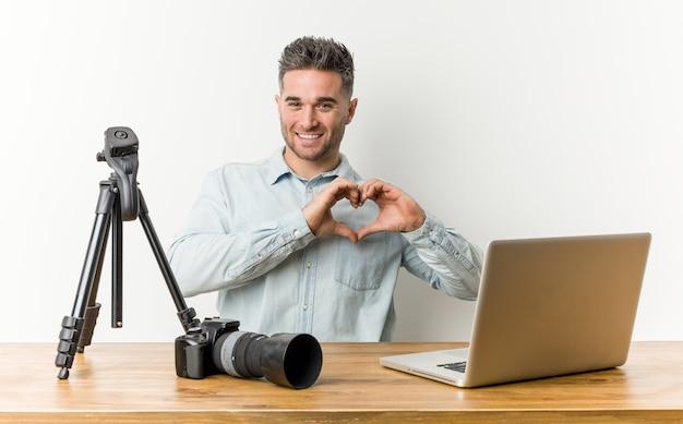 Jonge knappe fotografieleraar die en een hartvorm met handen glimlacht toont.