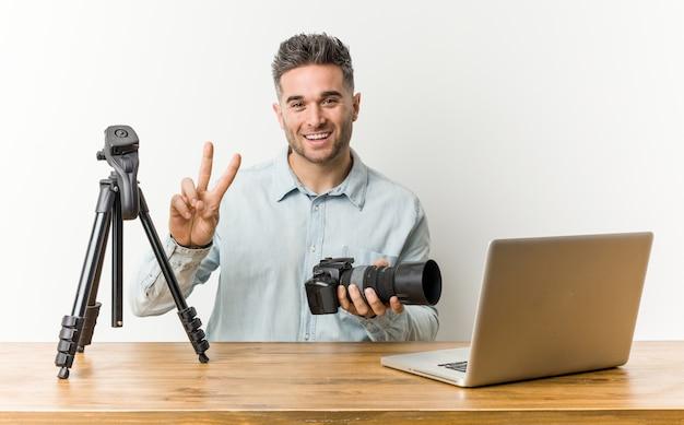 Jonge knappe fotografieleraar die nummer twee met vingers toont.