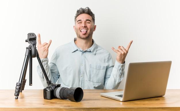 Jonge knappe fotografieleraar die rotsgebaar met vingers toont