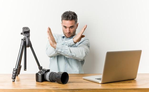 Jonge knappe fotografieleraar die twee wapens gekruist houden, ontkenningsconcept.