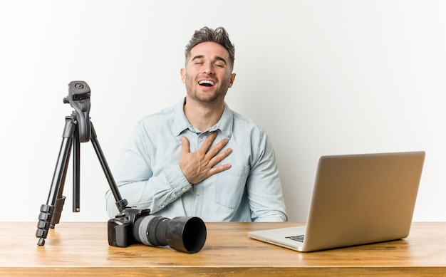 Jonge knappe fotografieleraar lacht hardop terwijl hij de hand op de borst houdt.