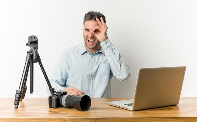 Jonge knappe fotografieleraar opgewonden het houden van ok gebaar op oog