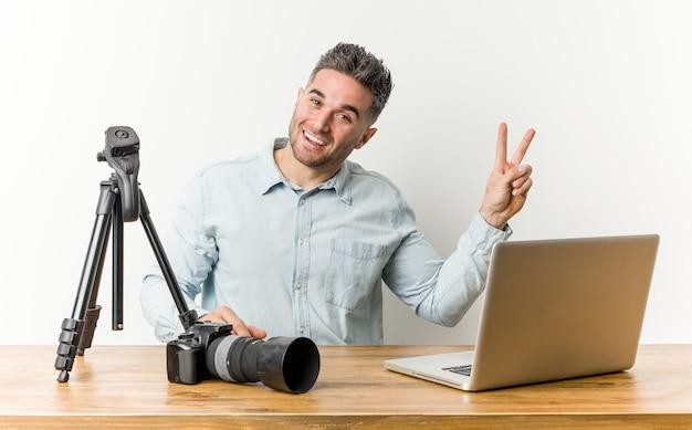 Jonge knappe fotografieleraar vrolijk en zorgeloos met een vredessymbool met vingers.