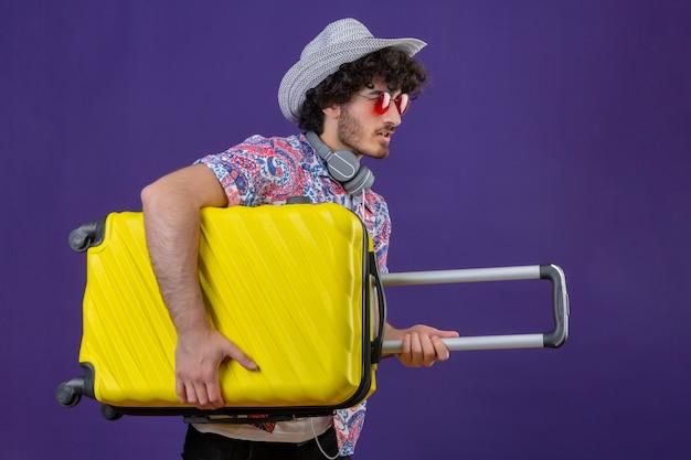 Jonge knappe gekrulde reiziger man met zonnebril, koptelefoon op nek en hoed met koffer staande in profiel te bekijken op geïsoleerde paarse muur