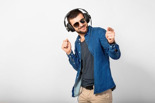 Jonge knappe gelukkig lachende man dansen en luisteren naar muziek in koptelefoon geïsoleerd op witte studio muur