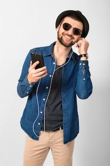 Jonge knappe gelukkig lachende man luisteren naar muziek in oortelefoons geïsoleerd op witte studio achtergrond, smartphone houden, denim shirt, hoed en zonnebril dragen