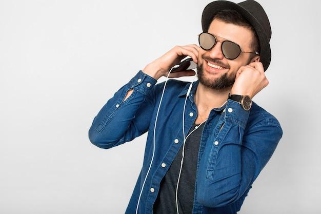 Jonge knappe gelukkig lachende man luisteren naar muziek in oortelefoons geïsoleerd op witte studio muur