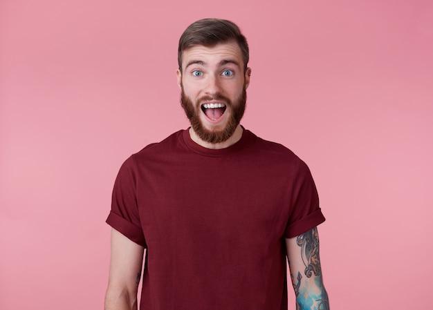 Jonge knappe gelukkig verbaasd rode bebaarde man in rood t-shirt, staat op roze achtergrond kijkt naar de camera met wijd open mond en ogen.