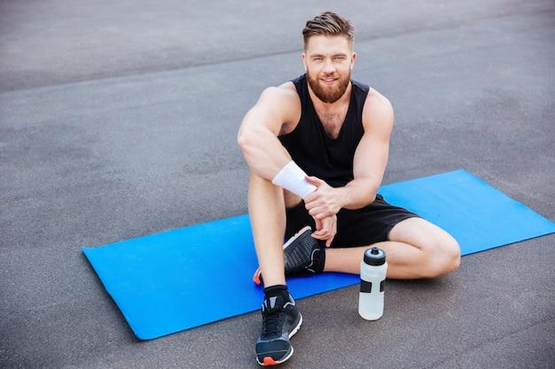 Jonge knappe gelukkige man atleet rust en drinkwater na training buitenshuis