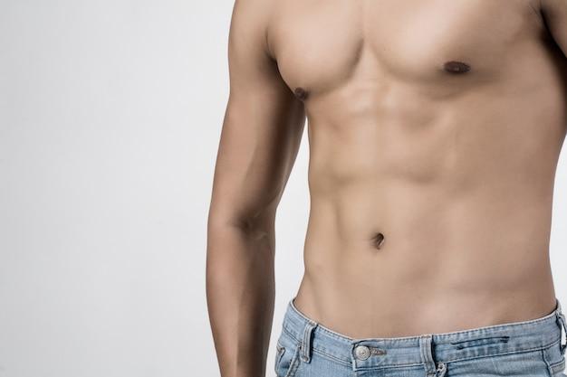 Jonge knappe geschikte mens die zijn die spieren stellen op witte achtergrond met copyspace worden geïsoleerd.