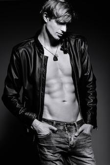 Jonge knappe gespierde fit mannelijk model man in lederen jas poseren in studio tonen zijn buikspieren