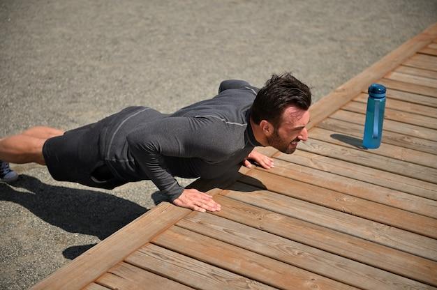 Jonge knappe gespierde sportman doet push-ups, pompen in zijn borstspieren. bovenaanzicht van sportman die buitenshuis traint