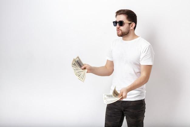 Jonge knappe glimlachende man met een baard in een wit overhemd met veel honderd-dollarbiljetten. geld