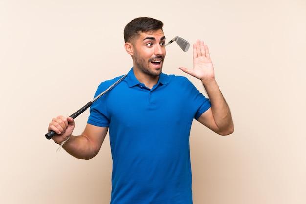 Jonge knappe golfspelermens die over geïsoleerde muur met wijd open mond schreeuwen