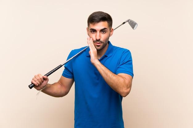 Jonge knappe golfspelermens over geïsoleerde muur die iets fluisteren