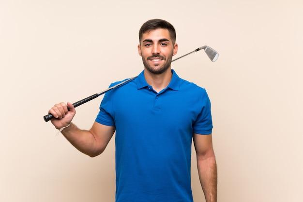 Jonge knappe golfspelermens over geïsoleerde muur die veel glimlacht