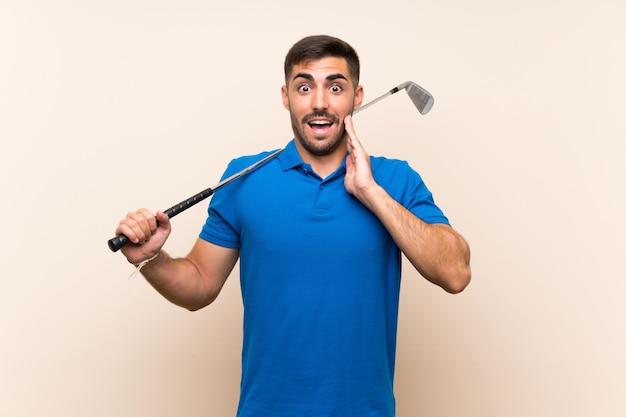 Jonge knappe golfspelermens over geïsoleerde muur met verrassing en geschokte gelaatsuitdrukking