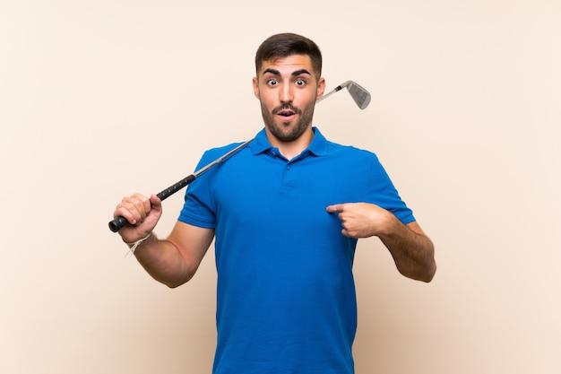 Jonge knappe golfspelermens over geïsoleerde muur met verrassingsgelaatsuitdrukking