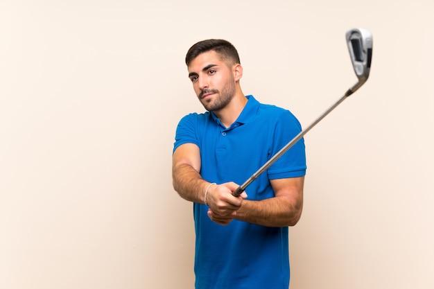 Jonge knappe golfspelermens over geïsoleerde muur