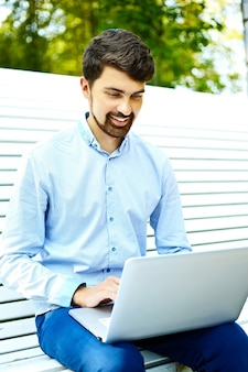 Jonge knappe het glimlachen zakenman modelzitting op de parkbank die laptop in toevallige hipsterdoek met behulp van