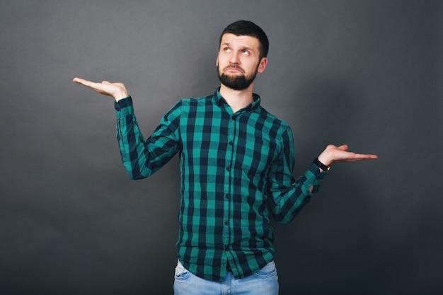Jonge knappe hipster bebaarde man hand in hand evaluatievraag, groen geruit overhemd, grijze achtergrond