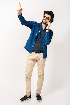 Jonge knappe hipster man staande praten over de telefoon