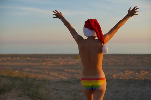Jonge knappe homoseksuele homo in regenboog lgbt vlag kleur slipje met kerstman kerstmuts staat op de zanderige kust met zijn rug en mooie billen naar de camera