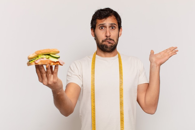 Jonge knappe indiaan die twijfelt of een onzekere uitdrukking heeft en een broodje vasthoudt