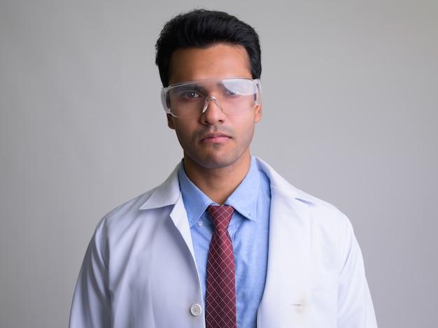 Jonge knappe indiase man arts met een beschermende bril op wit