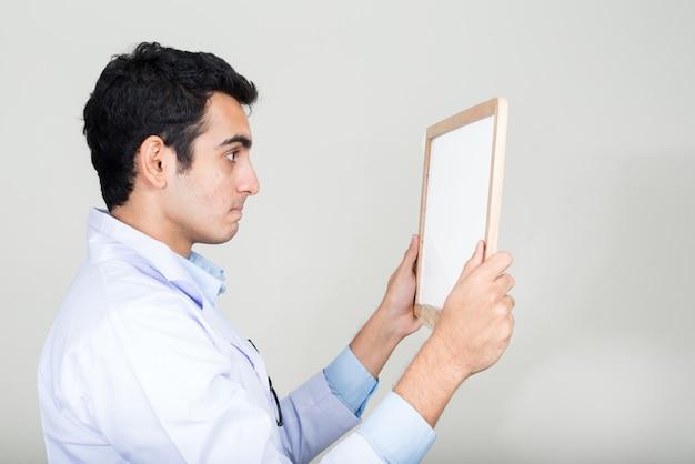 Jonge knappe indiase man arts tegen witte muur
