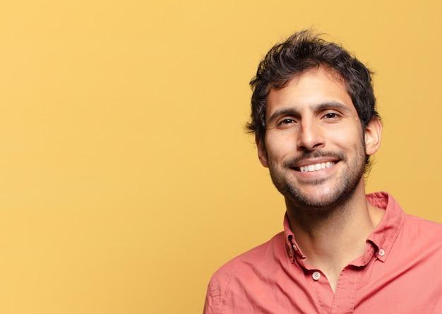 Jonge knappe indiase man blij en verrast uitdrukking