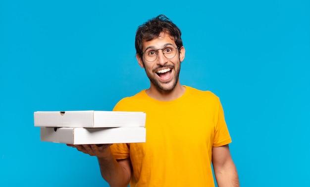 Jonge knappe indiase man blije uitdrukking en afhaalpizza's vasthouden?