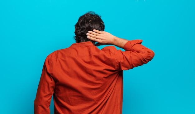 Jonge knappe indiase man denken of twijfelen, hoofd krabben, zich verbaasd en verward voelen, achter- of achteraanzicht
